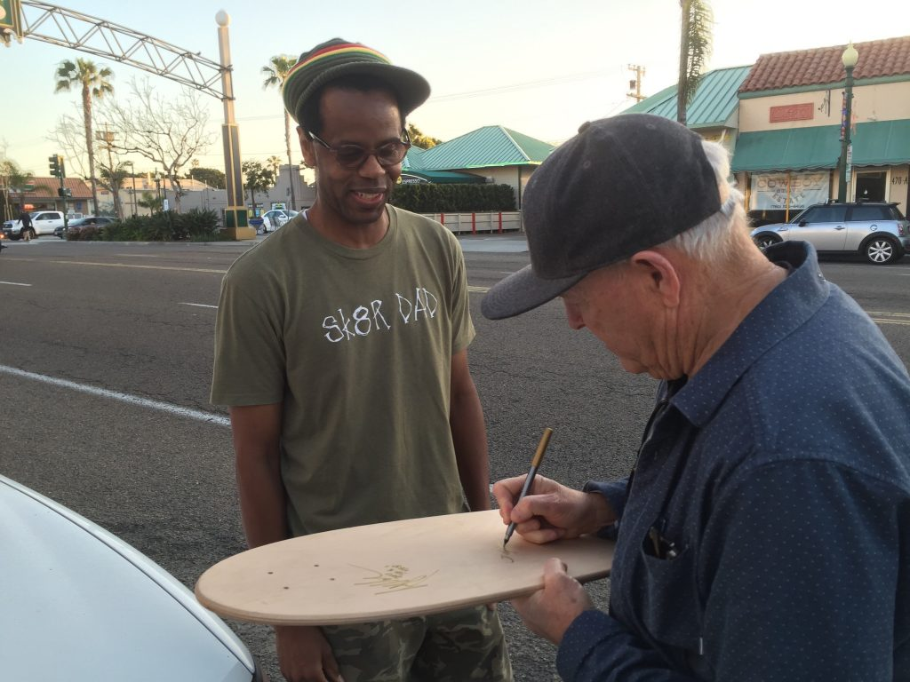 Grant signs a fan's skateboard